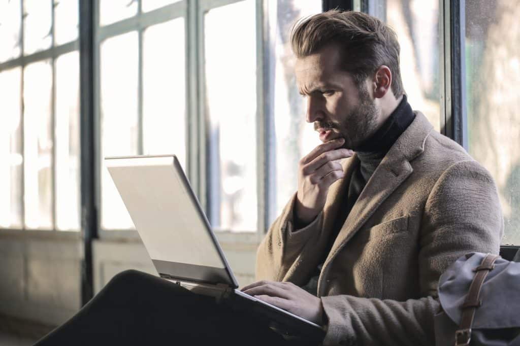 Homem com a mão direita no queixo e um notebook no colo, com a expressão pensativa enquanto olha para a tela.