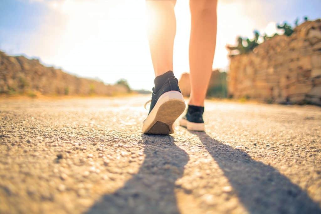 Pés de uma pessoa andando em uma rua