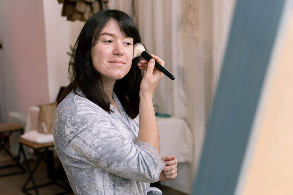 Mulher em frente a um espelho passando maquiagem