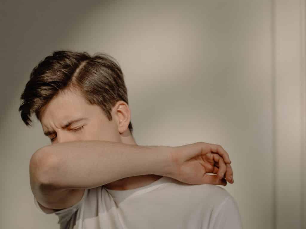 Homem doente tossindo no braço de olhos fechados.