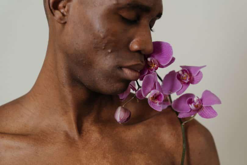 Homem de olhos fechados ao lado de uma flor