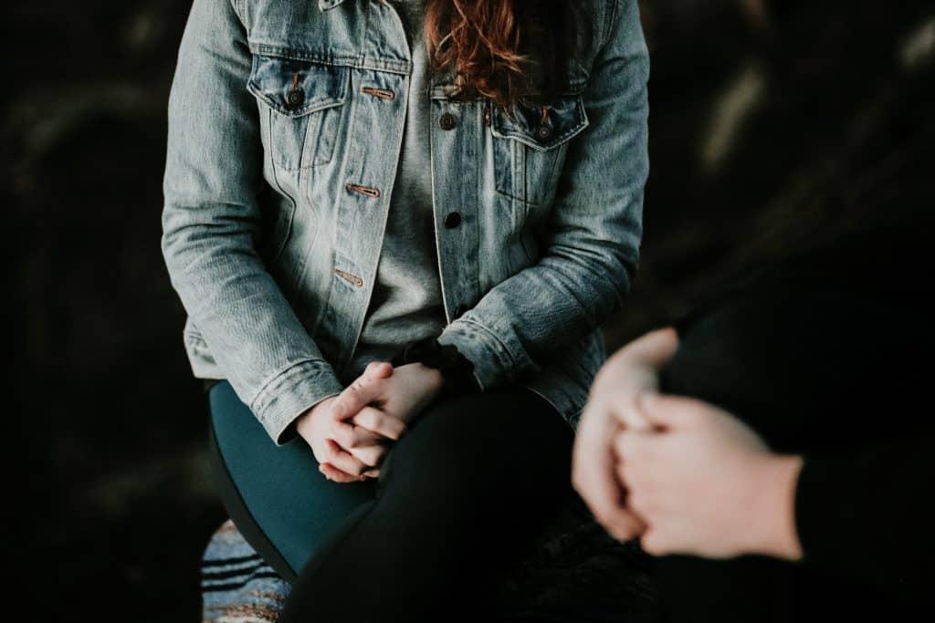 Mulher com pernas cruzadas ao lado de uma outra pessoa