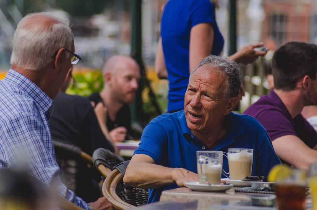 Dois homens sentados em uma cafeteria conversando.