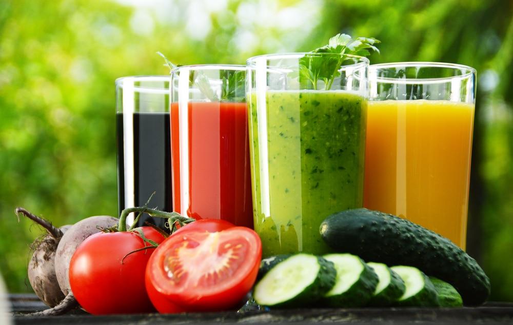 Quatro copos cheios de sucos de cores diferentes, e legumes na frente dos copos.