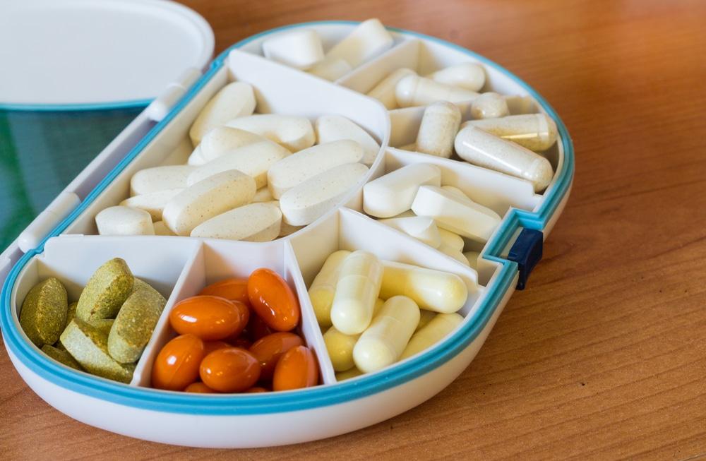 Recipiente com divisórias para remédios, cheio de pílulas e capsulas com cores diferentes.
