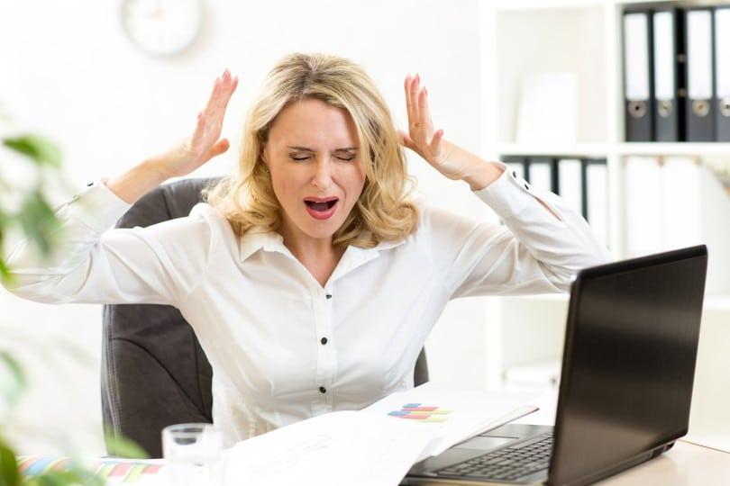 Mulher gritando com os olhos fechados e as mãos ao redor da cabeça.