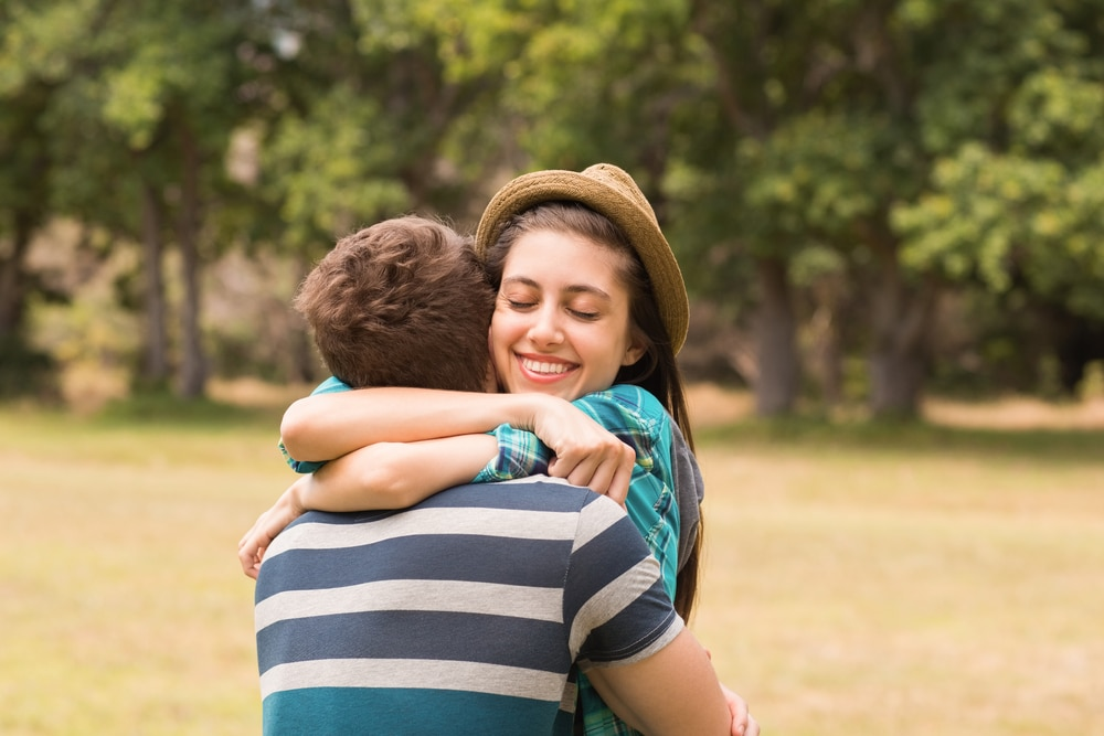 Menina adolescente abraçando menino em parque.