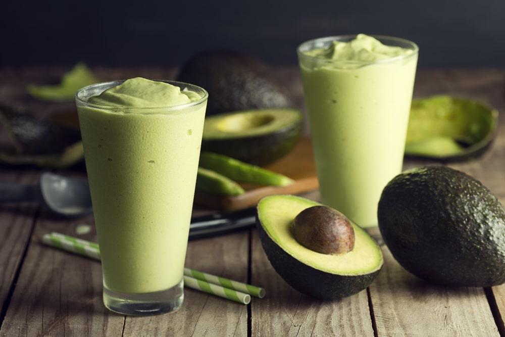Dois copos de vitamina de abacate, com várias metades de abacate entre elas.