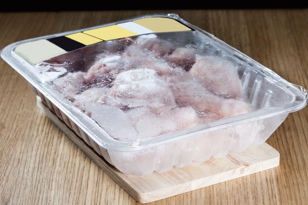 Pote com pedaços de frango congelados.