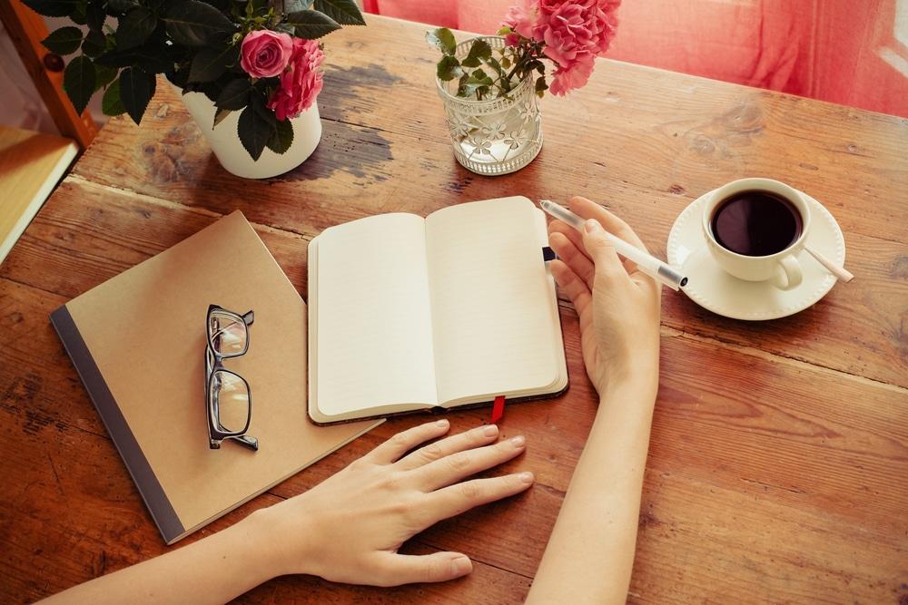 Pessoa escrevendo em caderno em uma mesa, com uma xícara de café e flores ao lado.