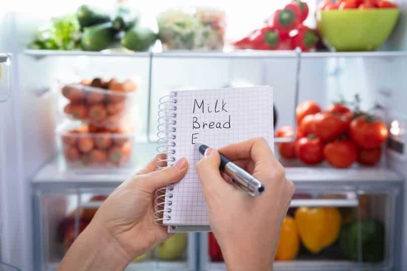 Mulher segurando uma lista com alimentos em frente a geladeira aberta