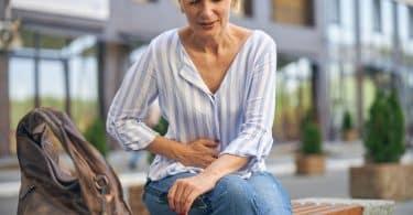 Mulher com forte dor de estômago.