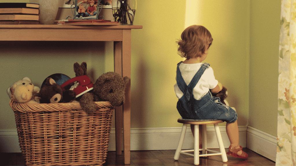 Menina de castigo sentada no canto no quarto