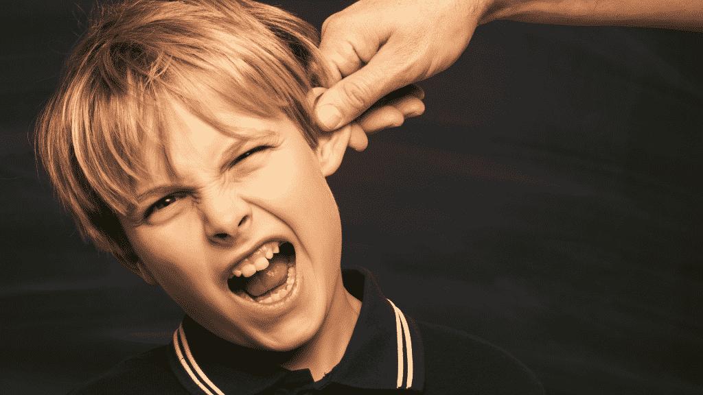 Criança sendo repreendida com puxão de orelha