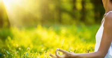 Braço de mulher meditando com fundo verde e sol refletindo