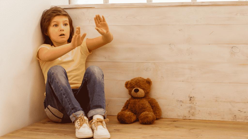 Criança com medo no canto da sala