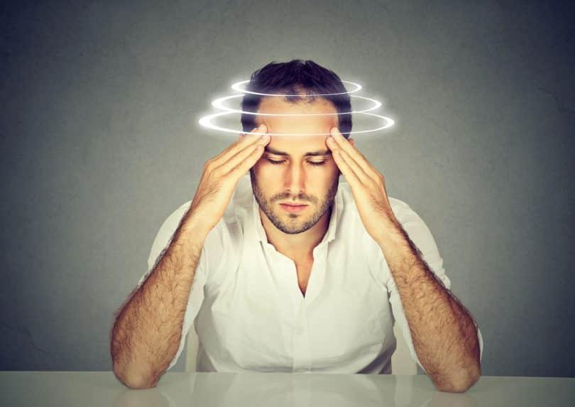 Homem branco com as mãos nas têmporas e auréolas brancas ao redor da cabeça.