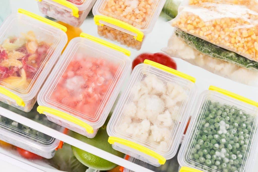 Potinhos com alimentos congelados no freezer