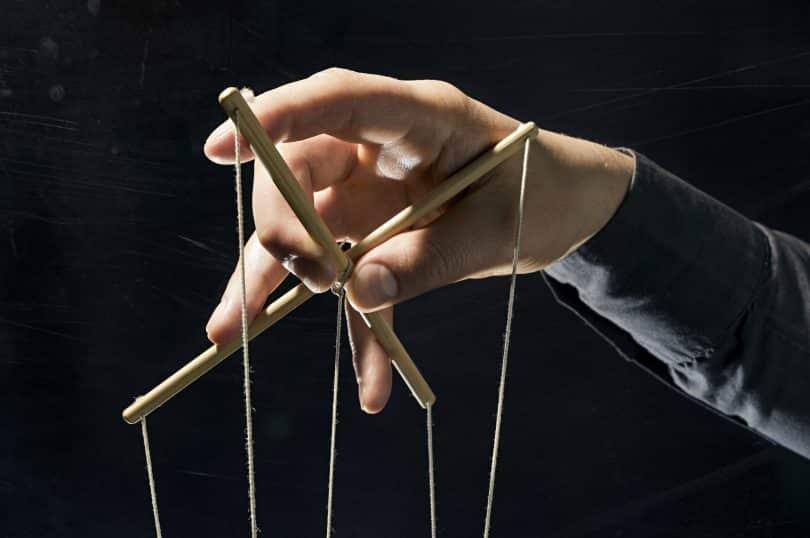 Mão segurando cordas de uma marionete.