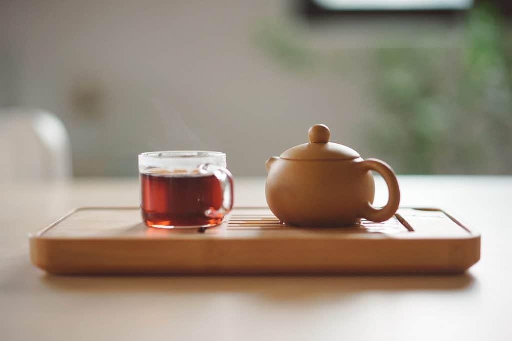 Tábua de madeira com uma xícara de vidro com um chá avermelhado.