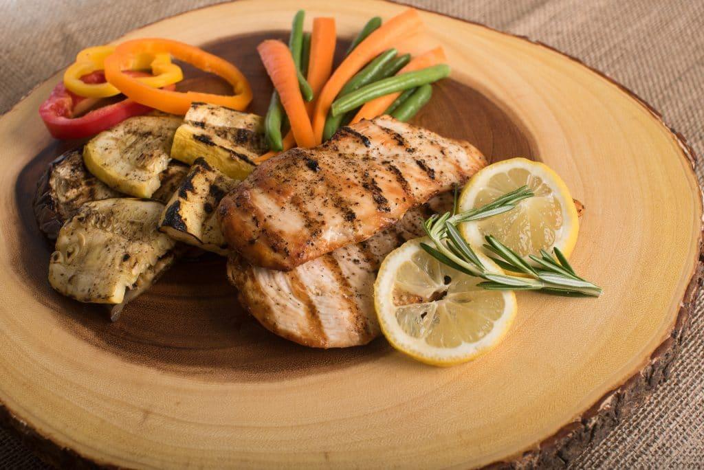 Prato com pedaços de frango e vegetais grelhados.