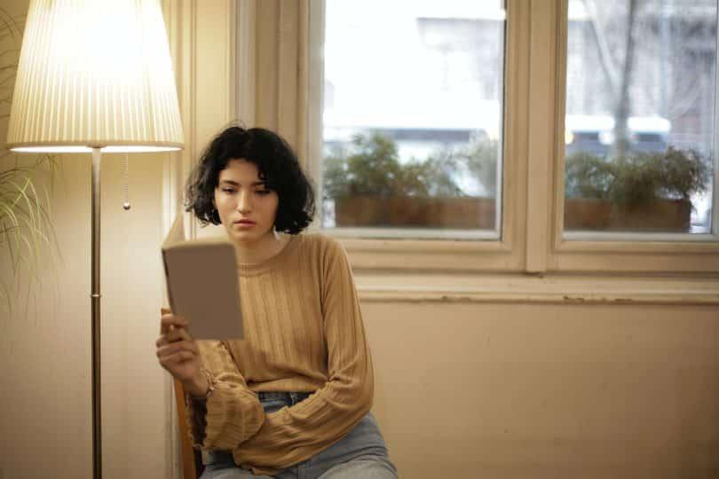 Mulher lendo um livro ao lado de um abajur