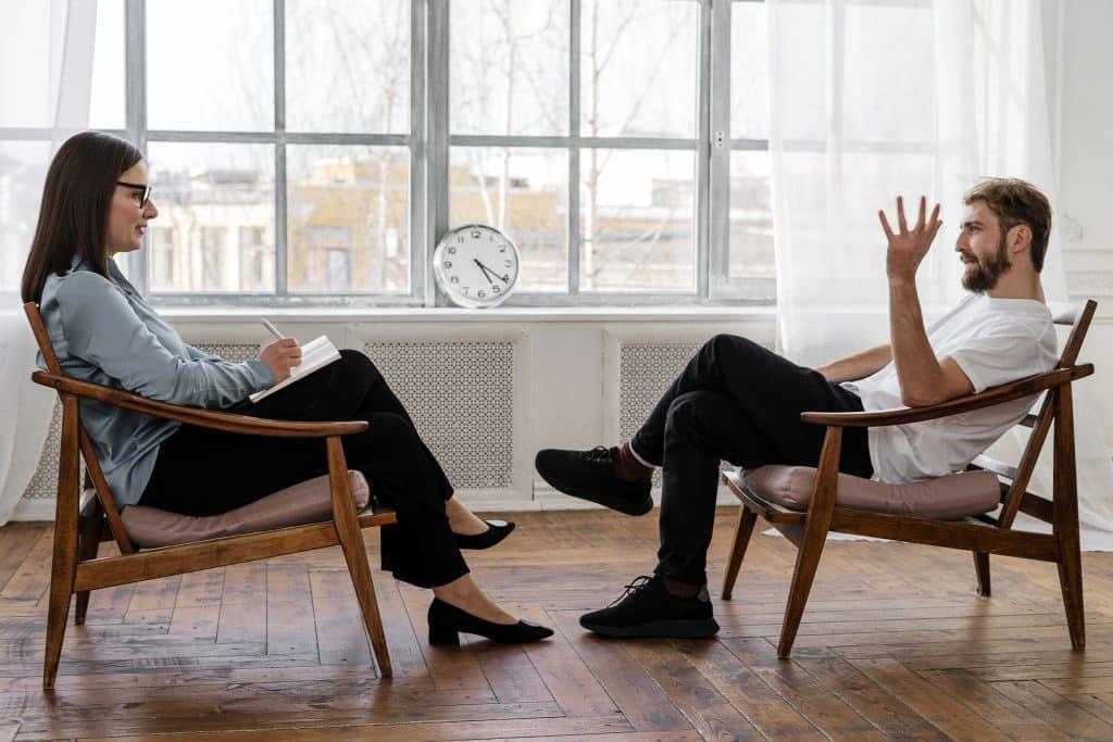 Homem sentado em uma cadeira conversando com psicologa a sua frente