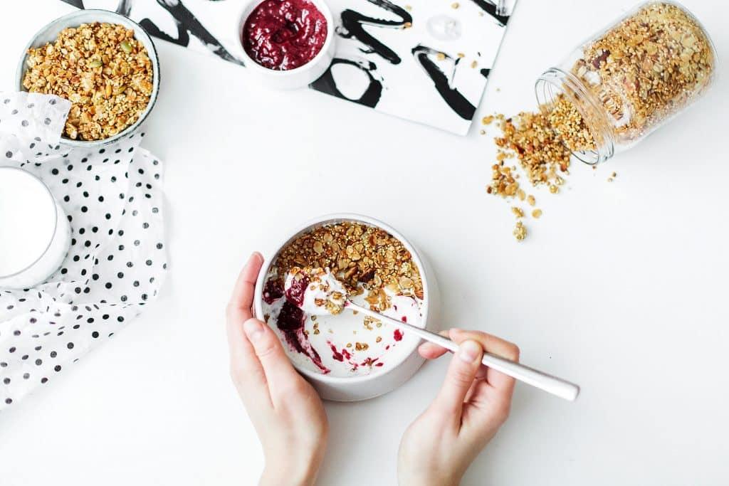 Mulher comendo iogurte com cereal
