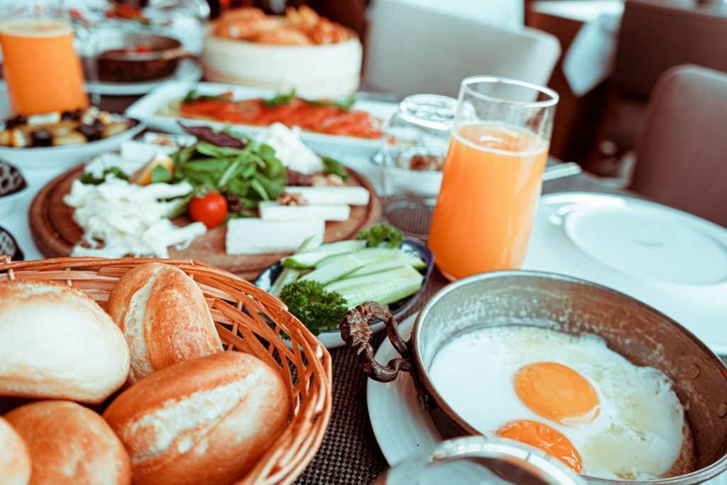 Mesa com ovos fritos, suco, pães