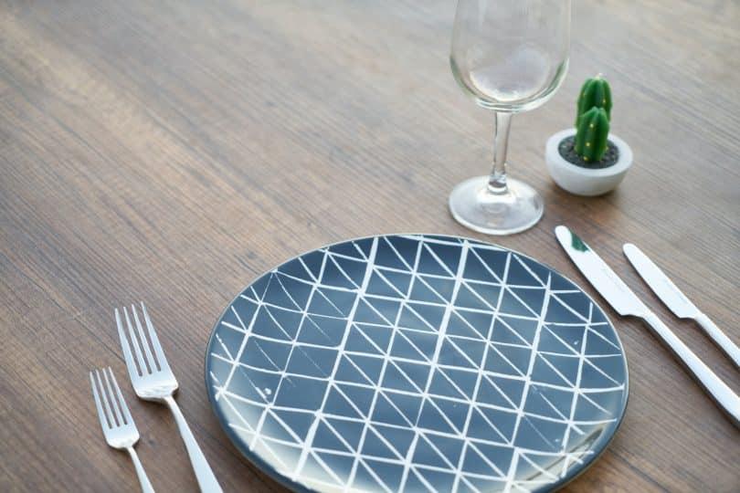 Prato na mesa com garfo e faca ao lado junto com uma taça de vinho