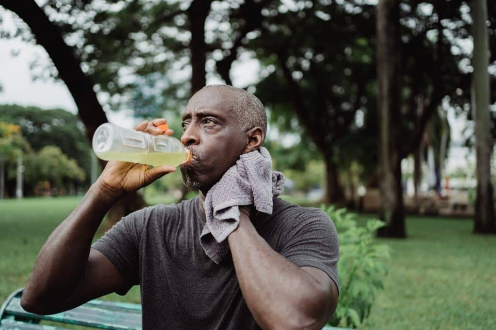 Homem negro tomando suco enquanto limpa o suor do rosto com uma toalha.