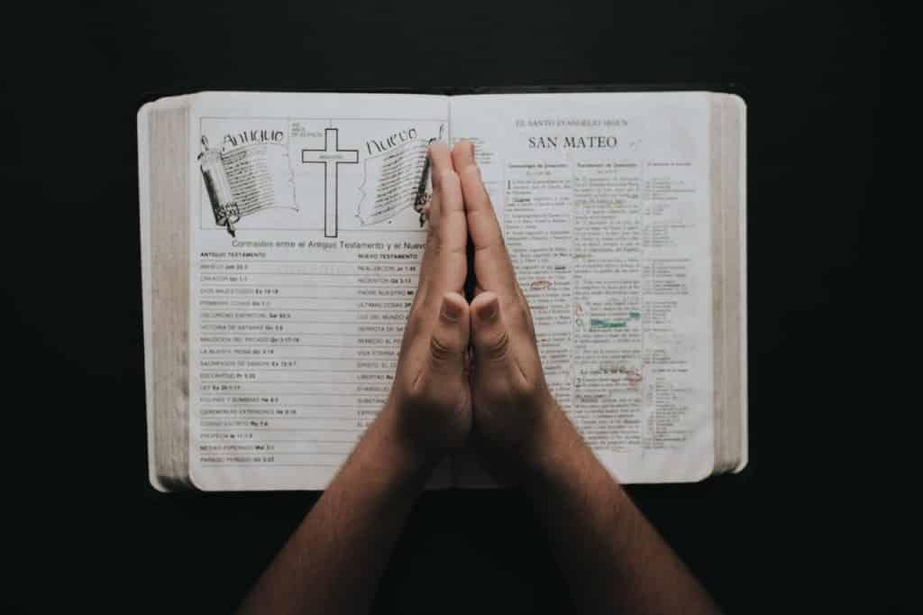 Pessoa com as mãos unidas sobre uma Bíblia.