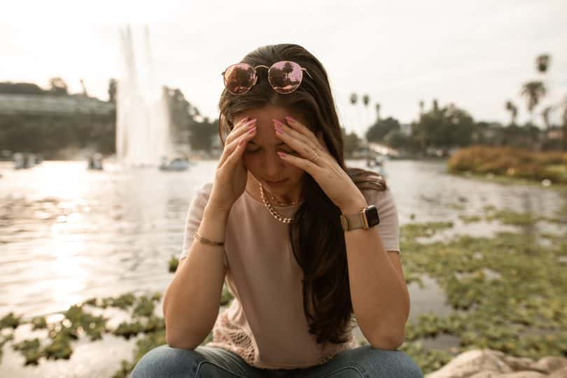 Mulher sentada ao lado de u m lago com as mãos na cabeça