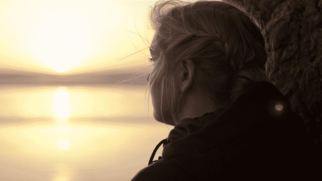 Mulher olhando pensativa para o horizonte