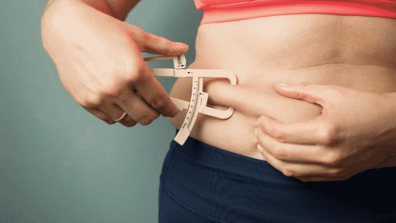 Mulher medindo a gordura na barriga