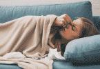 Mulher deitada pressionando as têmporas
