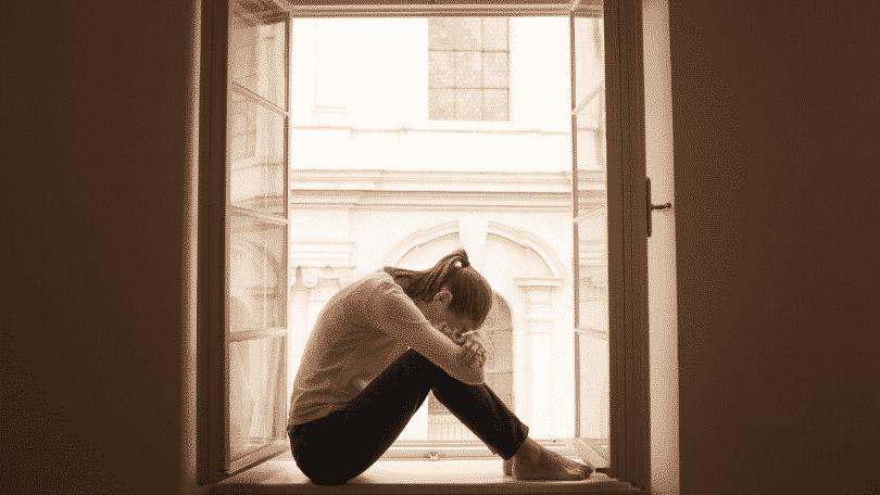 Mulher sentada na janela com a cabeça entre os joelhos