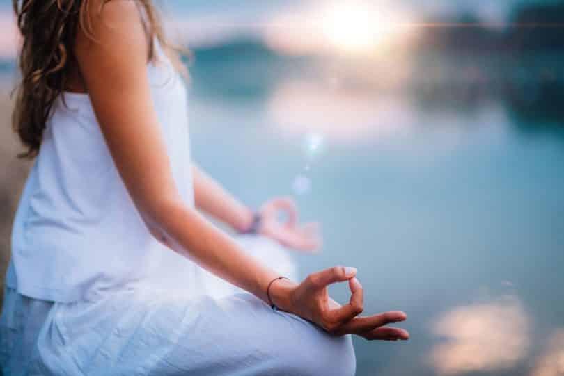 Mulher meditando próxima de um lago.