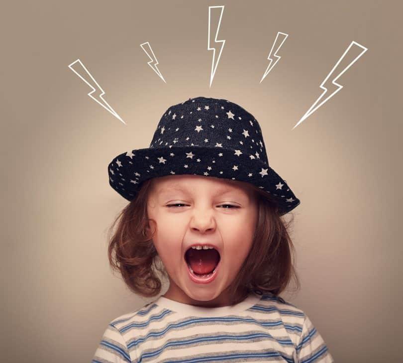 Criança com raiva gritando usando um chapéu