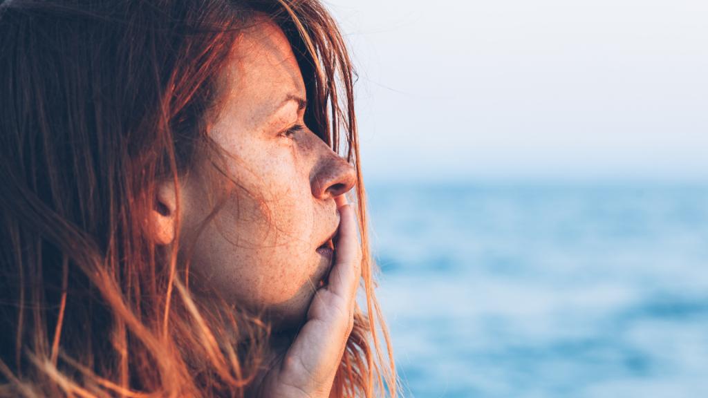 Mulher ruiva pensativa olhando para o mar