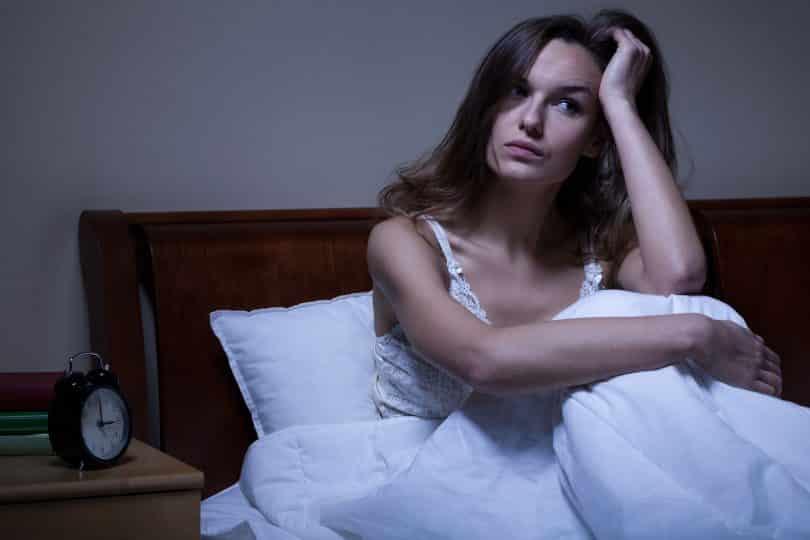 Mulher sentada na cama com insônia.