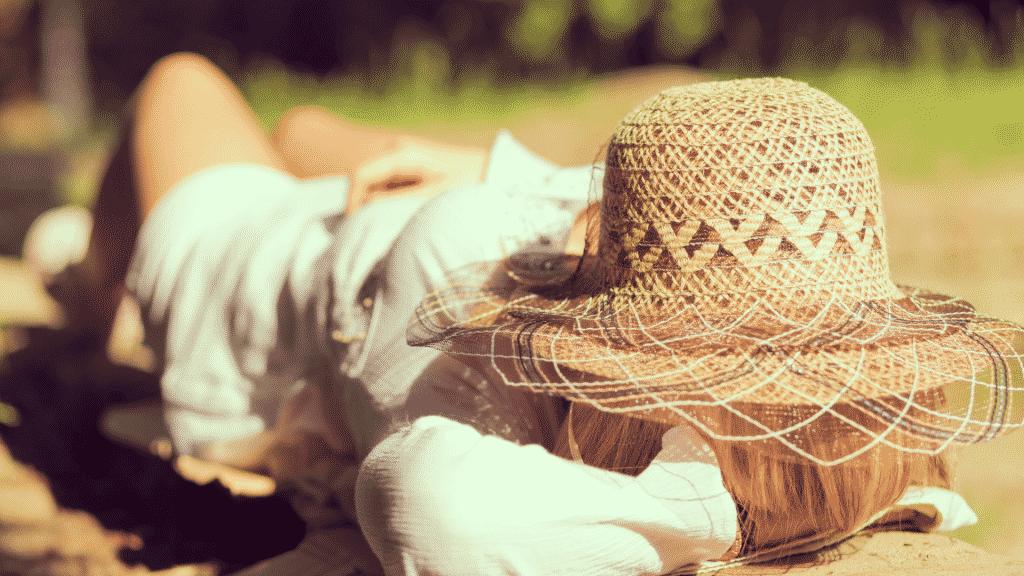 Mulher deitada no parque com chapéu de palha sobre o rosto
