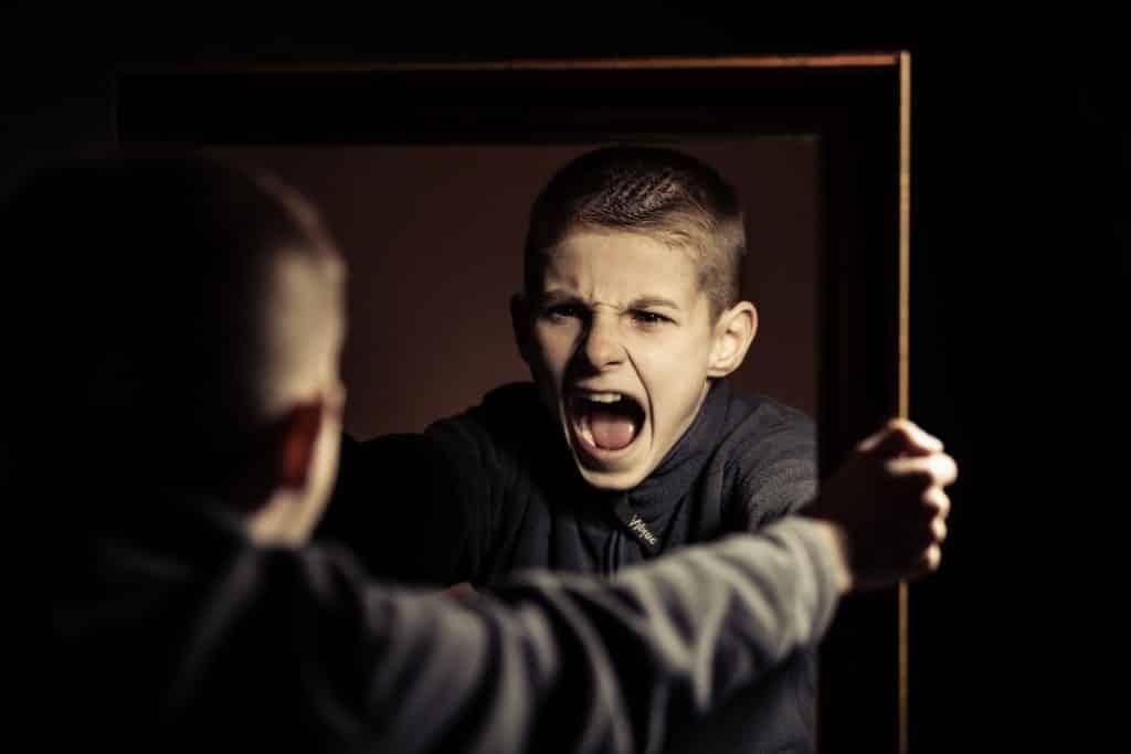 Menino com raiva gritando em frente ao espelho