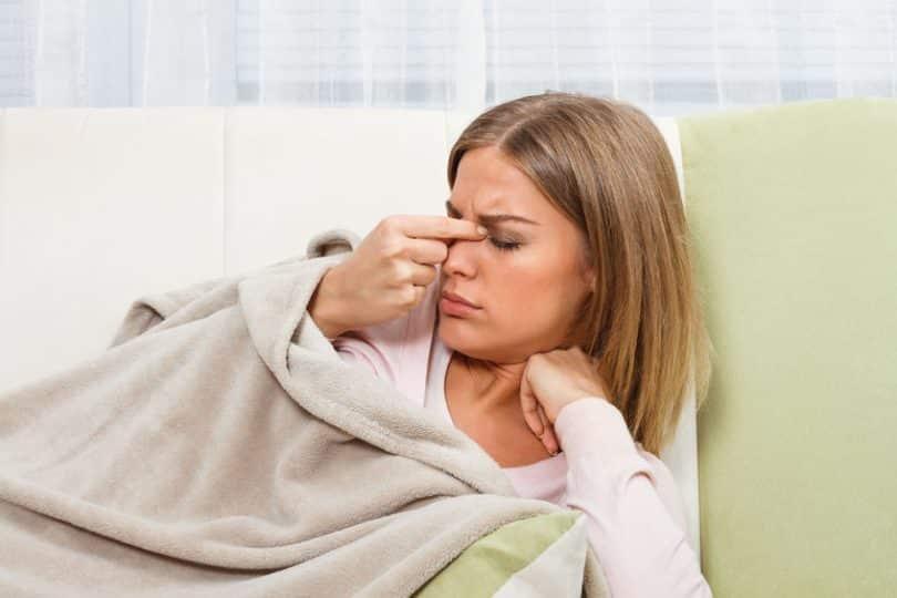 Mulher no sofá com cobertor e mão no nariz com olhos fechados