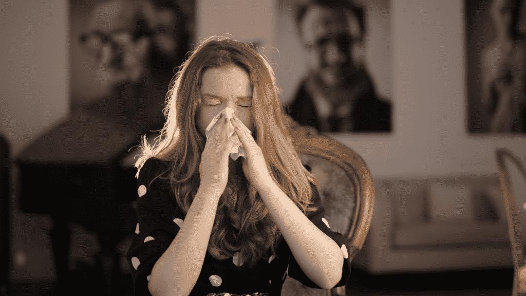 Mulher espirrando e assoando o nariz