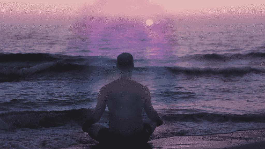 Aura colorida em volta de um homem meditando na praia
