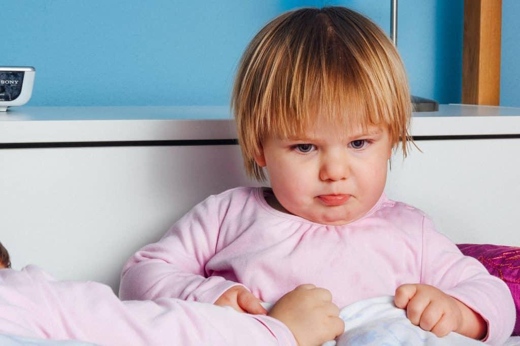 Criança olhando para baixo com tristeza em sua cama