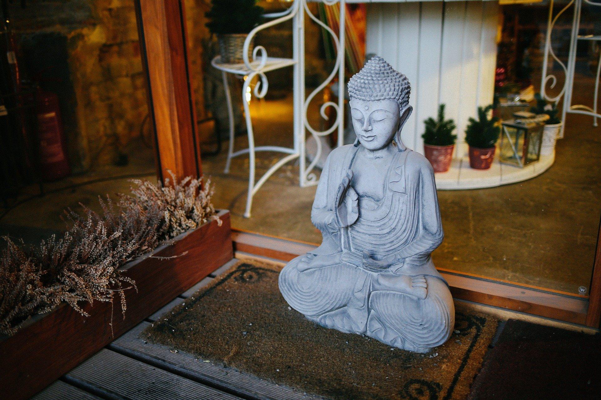 Estátua de Buda em cima de um tapete no quintal de uma casa.