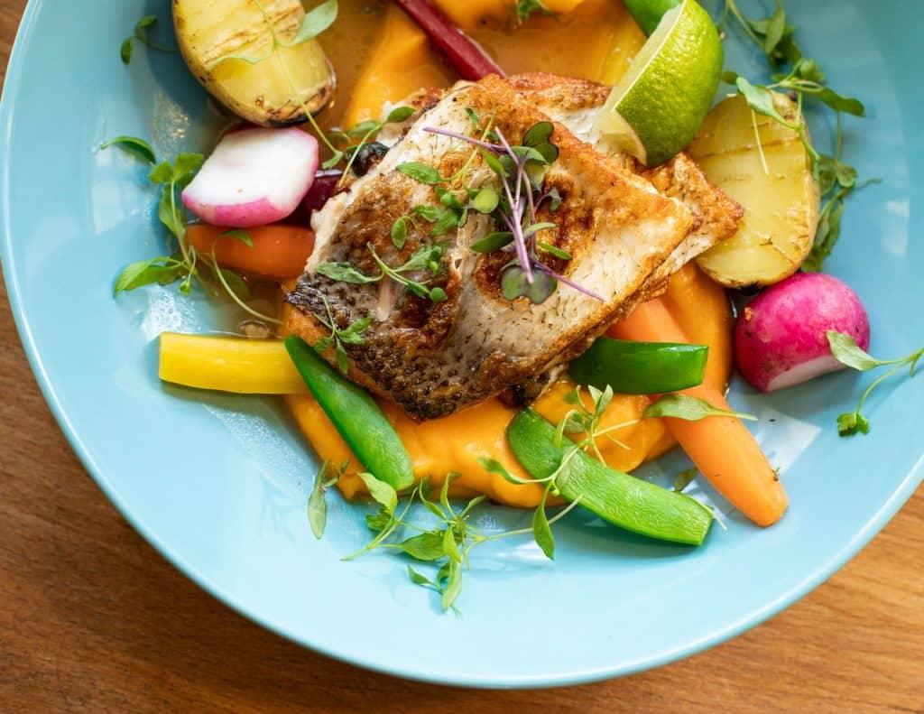 Prato com posta de peixe e vegetais.