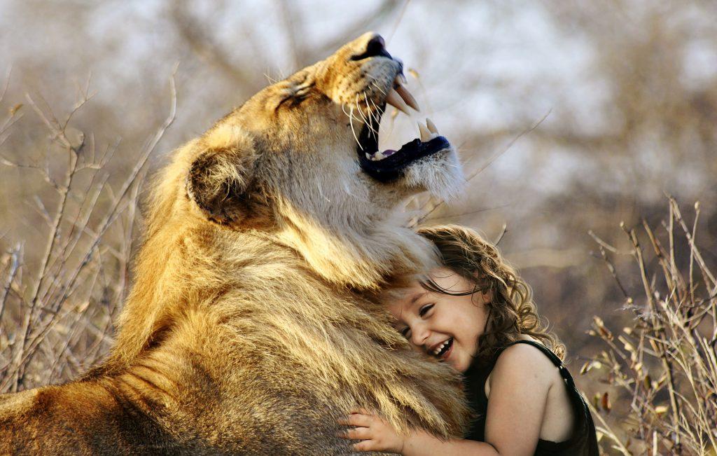 Menina sorrindo ao abraçar um leão.